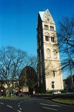 Im Vordergrund der erhalten gebliebene Turm mit der Bronzeplastik des Gekreuzigten, vom Düsseldorfer Künstler Bert Gerresheim, im Hintergrund das 1953 von Architekten Paul Schneider-Esleben geschaffene Gotteshaus als ein dreiteiliger Zentralbau, der mit einer kupfergedeckten Kuppel, eine Eiform, bekrönt wird.