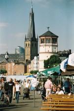 Urbanes Leben am Ufer des Rheins mit dem Schlossturm aus der Mitte des 16. Jahrhunderts und der St. Lambertus-Basilika, dessen Ursprünge bis ins 8. Jahrhundert zurück reichen.